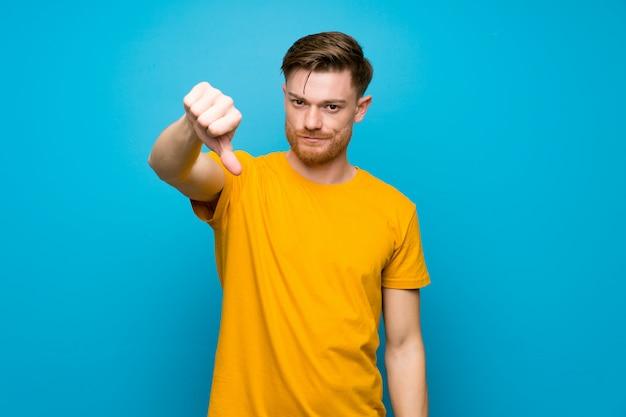 Hombre pelirrojo sobre pared azul mostrando pulgar hacia abajo con expresión negativa
