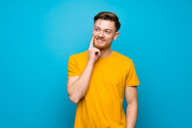 Hombre pelirrojo sobre pared azul pensando una idea mientras mira hacia arriba