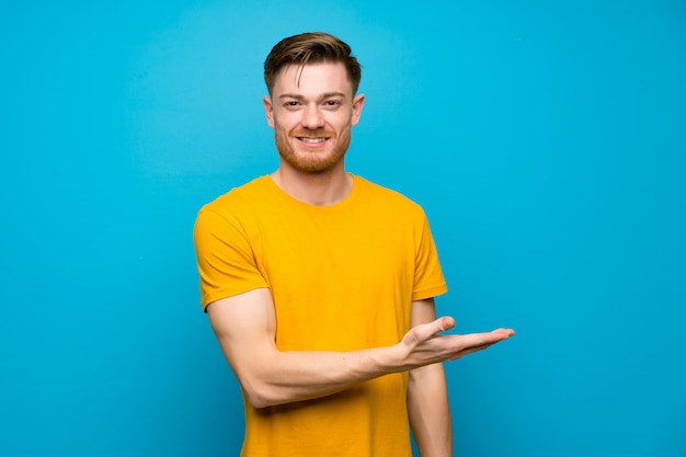 Hombre pelirrojo sobre pared azul presentando una idea mientras mira sonriente hacia