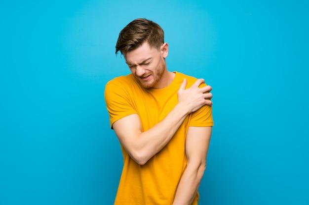 Hombre pelirrojo sobre pared azul que sufre de dolor en el hombro por haber hecho un esfuerzo