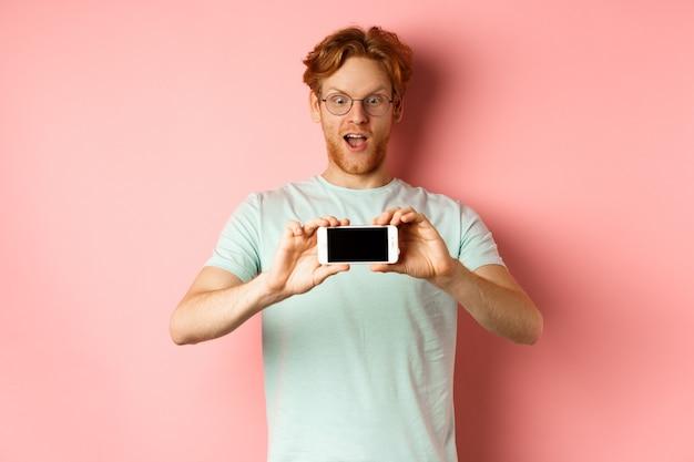 Hombre pelirrojo sorprendido jadeando y mirando con asombro teléfono, mostrando la pantalla del teléfono inteligente en blanco horizontalmente, de pie sobre fondo rosa.