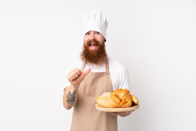 Hombre pelirrojo en uniforme de chef. hombre panadero sosteniendo una mesa con varios panes apuntando a un lado para presentar un producto
