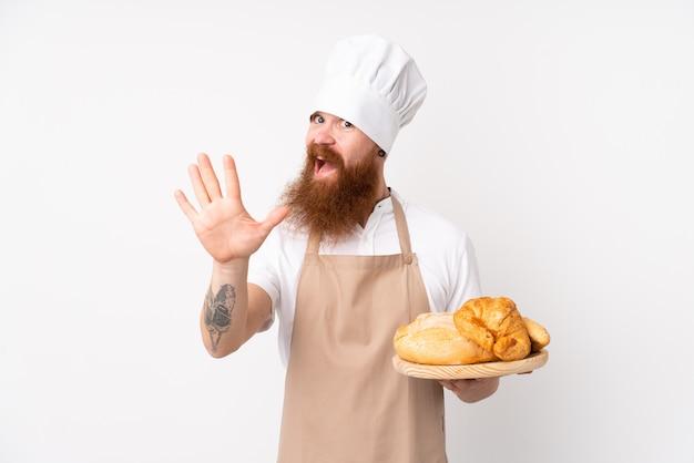 Hombre pelirrojo en uniforme de chef. hombre panadero sosteniendo una mesa con varios panes saludando con la mano con expresión feliz