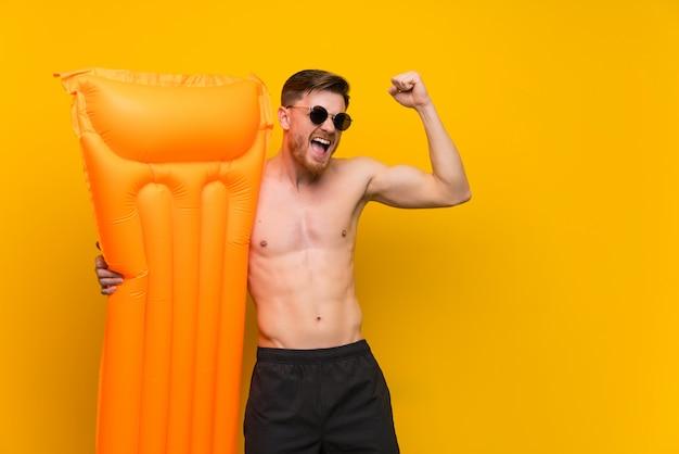Hombre pelirrojo en vacaciones de verano celebrando una victoria.