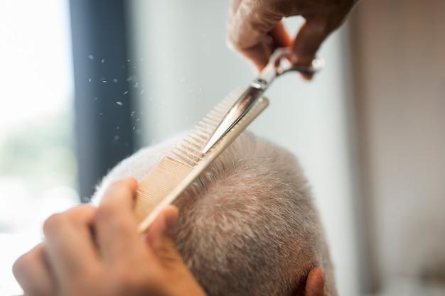 Hombre del pelo del corte de la peluquería en salón