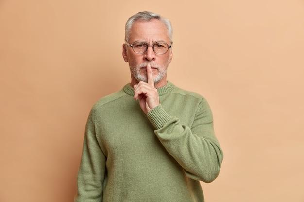 Hombre de pelo gris barbudo mira seriamente al frente hace un gesto de silencio pide guardar silencio mira con confianza al frente usa lentes transparentes y un jersey casual aislado sobre una pared marrón