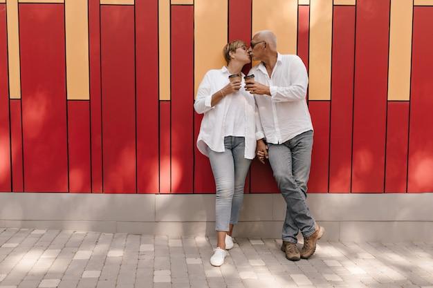 Hombre de pelo gris con camisa blanca y jeans sosteniendo una taza de té y besando a su esposa con el pelo corto en ropa ligera en rojo y naranja.