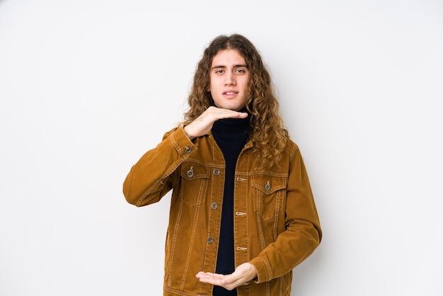 Hombre de pelo largo posando aislado sosteniendo algo con ambas manos, presentación del producto.