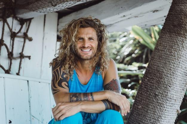 Un hombre con pelo largo y rizado en un lugar de pesca. pescador en el oceano
