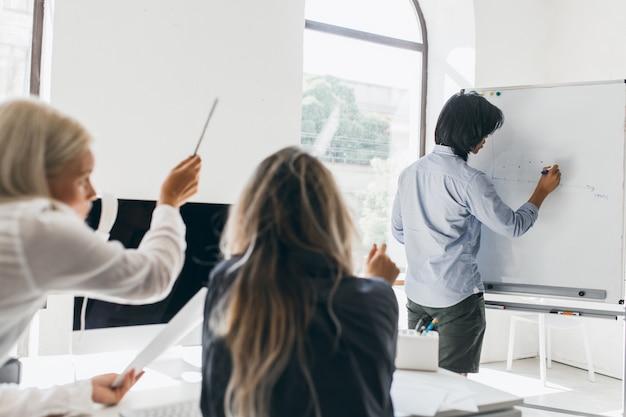 Hombre de pelo oscuro dibujo infografía en rotafolio de pie en la sala de conferencias
