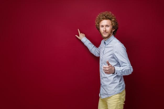 Hombre de pelo rizado en camisa mostrando espacio en blanco con el dedo índice