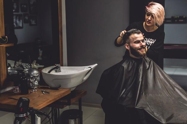 Hombre de peluquería mujer en barbería