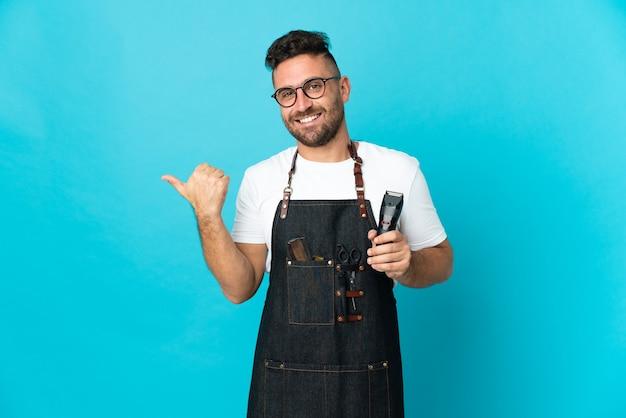 Hombre de peluquero en un delantal apuntando hacia el lado para presentar un producto
