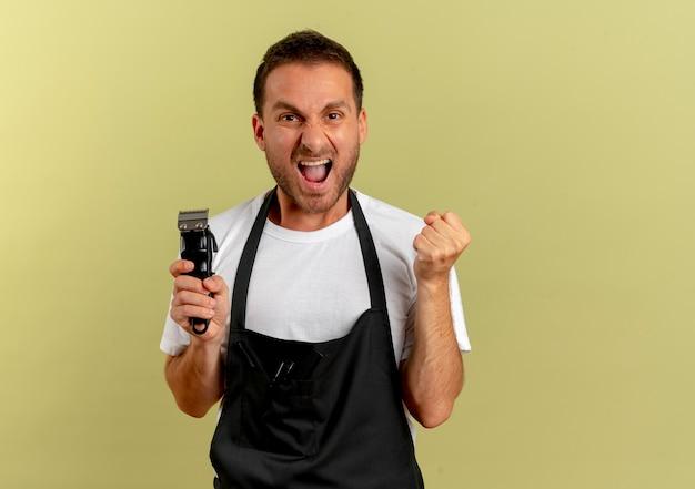 Hombre de peluquero en delantal sosteniendo la máquina de corte de pelo apretando el puño feliz y emocionado de pie sobre la pared de luz