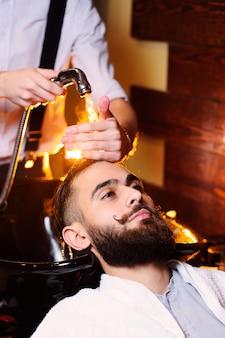 Hombre peluquero lava cliente