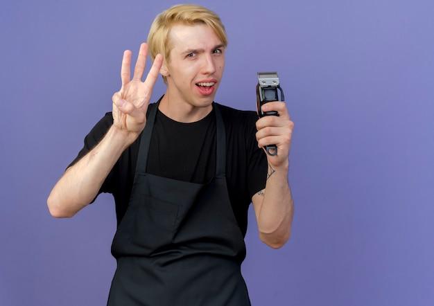 Hombre de peluquero profesional en delantal sosteniendo recortadora mostrando y apuntando hacia arriba con los dedos número tres