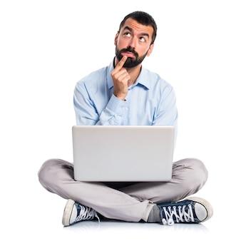 Hombre con el pensamiento de la computadora portátil