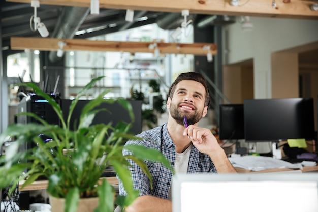 Hombre de pensamiento feliz en coworking de oficina mientras usa la computadora portátil