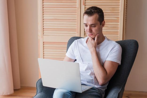 Hombre de pensamiento que se sienta en silla y que usa el ordenador portátil en sitio