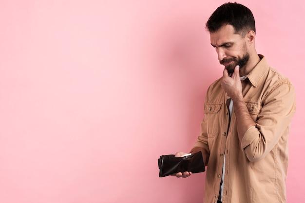 Hombre pensando mientras sostiene la billetera vacía