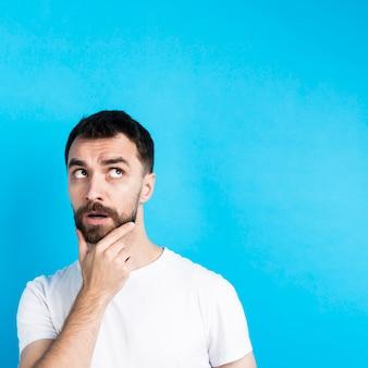 Hombre pensante posando con la mano en el mentón