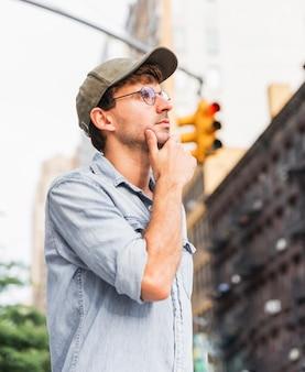 Hombre pensante sosteniendo su mano debajo de su barbilla