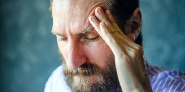 Hombre pensativo con barba masajea el templo izquierdo