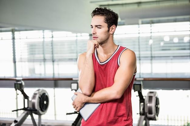 Hombre pensativo con la barbilla en el puño en el gimnasio