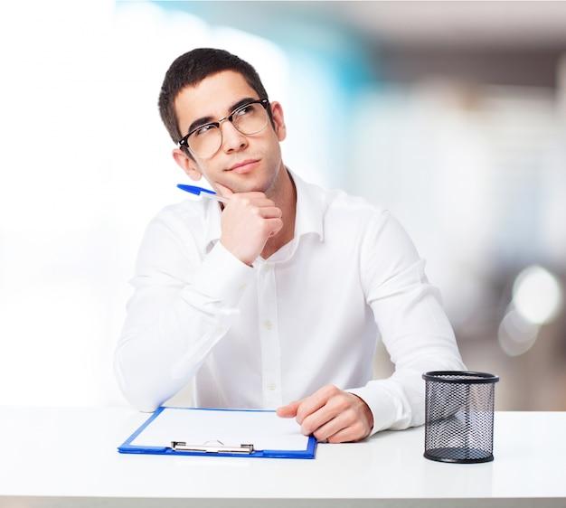 Hombre pensativo con un bolígrafo y una tabla de comprobación