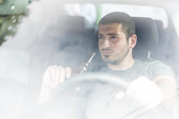 Hombre pensativo con cerveza conduciendo coche