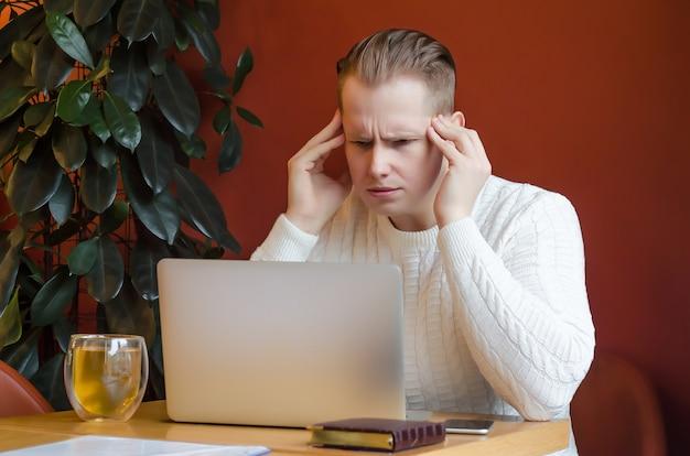 Hombre pensativo, estresado, molesto, mira fijamente a la computadora portátil, tenencias en la cabeza. trabajo remoto. teletrabajo noticias impactantes. quédate en casa. emociones humanas. crisis económica