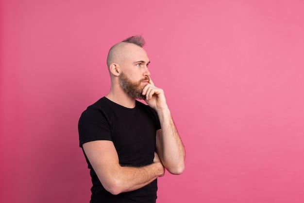 Hombre pensativo europeo en estudio sobre fondo rosa