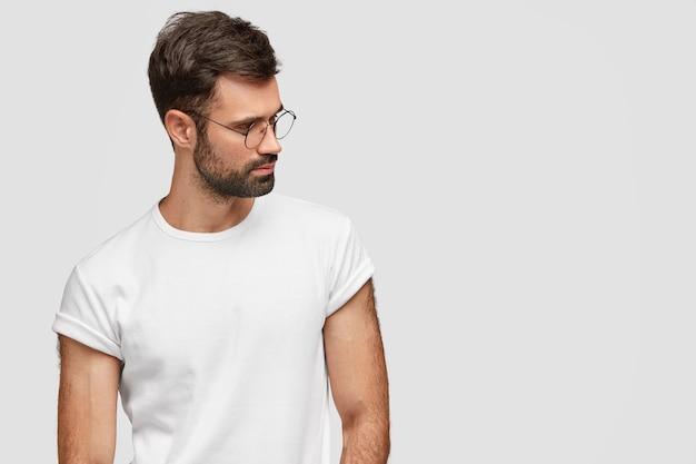 Hombre pensativo con forma de cuerpo fuerte, enfocado a un lado con expresión pensativa