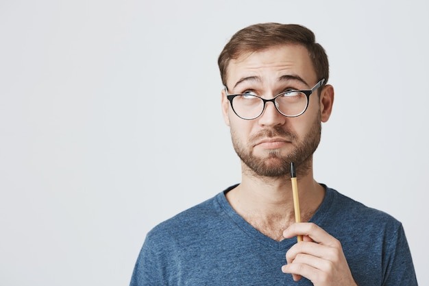 Hombre pensativo con gafas buscando inspiración, sostenga el lápiz y mire hacia otro lado