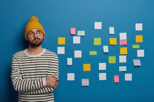 Hombre pensativo con gafas, sombreros amarillos y un jersey de rayas tiene una ocupación creativa, se centró arriba, se para con las manos cruzadas