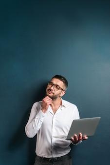 Hombre pensativo con gafas usando la computadora portátil.