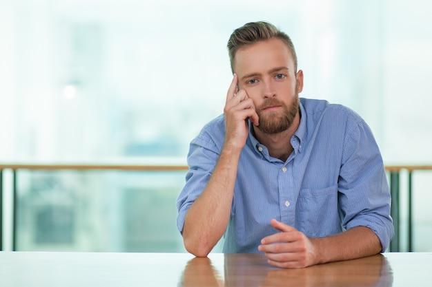 Hombre pensativo joven que se sienta en el vector del café vacía