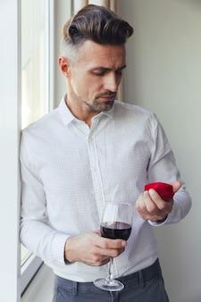 Hombre pensativo joven que sostiene el vidrio con el vino y que mira la caja con el anillo