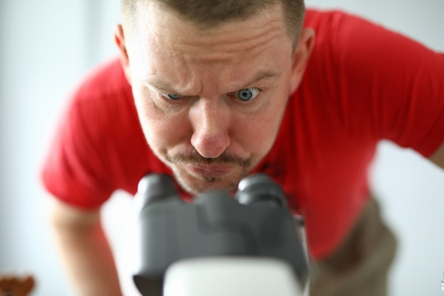 Hombre pensativo mira atentamente a través del microscopio