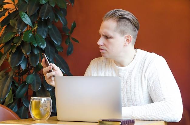 El hombre pensativo mira fijamente el teléfono inteligente, trabaja remotamente en una computadora portátil y recibe malas noticias. crisis económica mundial autoaislamiento, quiebra.