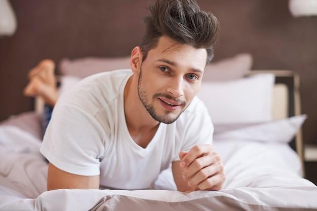 Hombre pensativo relajante en su acogedor dormitorio