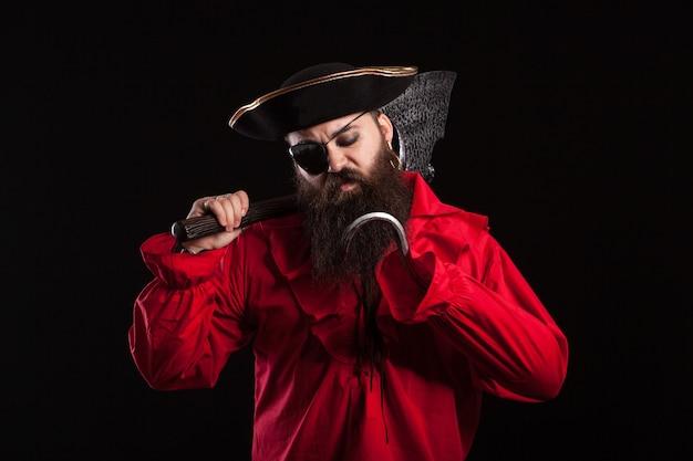 Hombre pensativo con ropa de pirata para carnaval con un gancho en la mano. hombre disfrazado de ladrón caribeño.