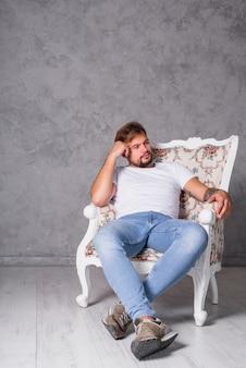 Hombre pensativo sentado en sillón