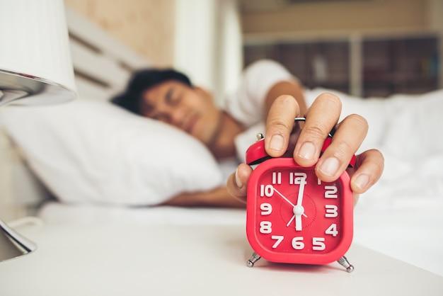 Hombre perezoso despertándose en su habitación.
