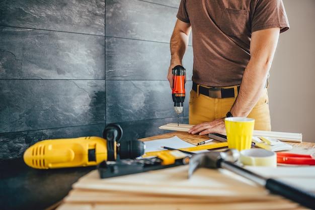 Hombre perforando madera con batería taladro