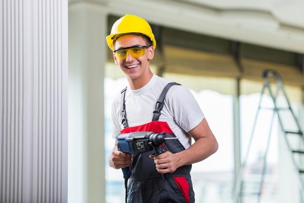 Hombre perforando la pared con taladro perforador