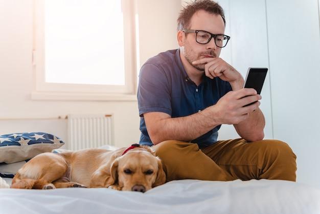 Hombre y el perro en la cama
