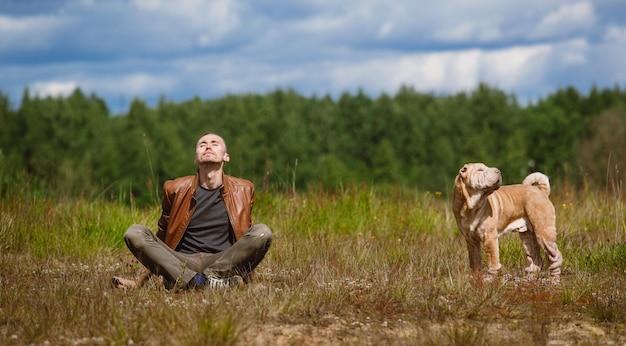 Hombre y un perro de raza shar pei sentado en el suelo