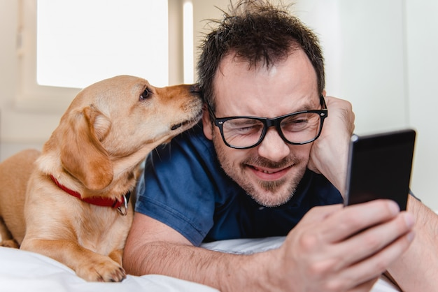 Hombre con el perro usando un teléfono inteligente en la cama