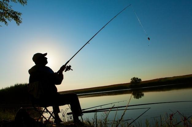 El hombre pesca en un lago